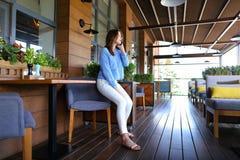 Chica joven que habla por smartphone en el restaurante Fotos de archivo