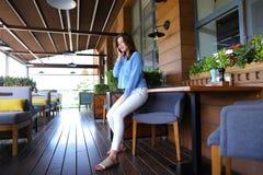 Chica joven que habla por smartphone en el restaurante Imagen de archivo libre de regalías