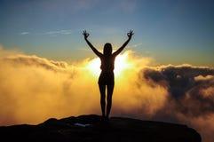 Chica joven que hace actitud de la yoga en las nubes en la puesta del sol Sano Imagen de archivo