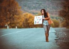 Chica joven que hace autostop con el cartel Imagenes de archivo