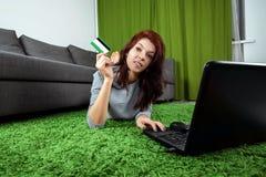 Chica joven que hace compras en l?nea mientras que se sienta en casa El concepto de compras en l?nea, tienda en l?nea que hace co fotografía de archivo