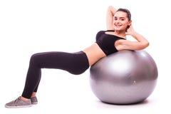 Chica joven que hace ejercicio con la bola de los pilates Foto de archivo