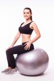 Chica joven que hace ejercicio con la bola de los pilates Fotos de archivo