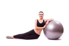 Chica joven que hace ejercicio con la bola de los pilates Foto de archivo libre de regalías