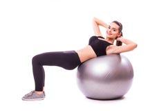 Chica joven que hace ejercicio con la bola de los pilates Imágenes de archivo libres de regalías