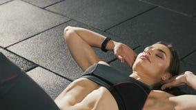 Chica joven que hace ejercicios en el gimnasio, haciendo pectorales del ABS metrajes