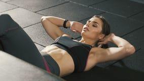 Chica joven que hace ejercicios en el gimnasio, haciendo pectorales del ABS almacen de video