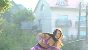 Chica joven que hace el ejercicio activo para la flexibilidad de la espina dorsal en la calle lentamente almacen de video