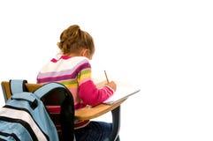 Chica joven que hace el trabajo de la escuela en el escritorio Fotografía de archivo
