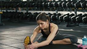 Chica joven que hace estirando ejercicios en gimnasio almacen de metraje de vídeo