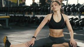 Chica joven que hace estirando ejercicios en gimnasio metrajes