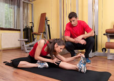 Chica joven que hace estirando ejercicios en la gimnasia Imagenes de archivo