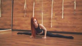 Chica joven que hace estirar mientras que se sienta en el piso metrajes