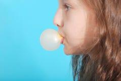 Chica joven que hace la burbuja con el chicle Fotografía de archivo libre de regalías