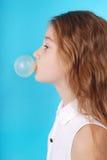 Chica joven que hace la burbuja con el chicle Fotos de archivo libres de regalías