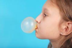 Chica joven que hace la burbuja con el chicle Foto de archivo libre de regalías