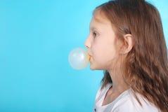 Chica joven que hace la burbuja con el chicle Foto de archivo