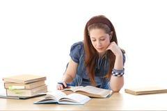 Chica joven que hace la preparación en el escritorio Imagen de archivo libre de regalías