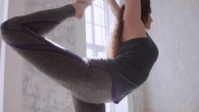 Chica joven que hace la yoga, estirando la clase, forma de vida sana metrajes