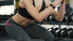 Chica joven que hace los ejercicios en gimnasio, exercies de los pelotones, metrajes