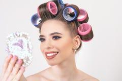 Chica joven que hace maquillaje y el peinado usando los bigudíes Fotografía de archivo libre de regalías