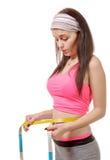 Chica joven que hace medida alrededor de su cintura con la cinta métrica Imagenes de archivo