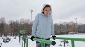 Chica joven que hace pectorales en las barras Invierno almacen de metraje de vídeo