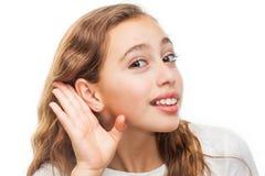 Chica joven que hace un gesto que escucha aislado imagen de archivo libre de regalías
