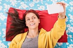 Chica joven que hace un selfie en su cama Imagenes de archivo