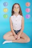 Chica joven que hace una burbuja grande con un chicle Imagenes de archivo