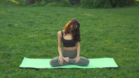 Chica joven que hace yoga en el parque metrajes