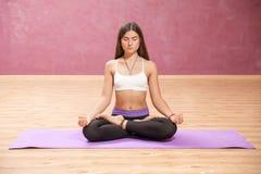 Chica joven que hace yoga en la posición de loto dentro Imagen de archivo