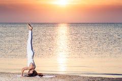 Chica joven que hace yoga en la salida del sol en la playa foto de archivo libre de regalías