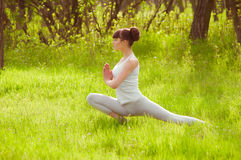 Chica joven que hace yoga en una hierba verde Fotos de archivo libres de regalías