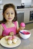 Chica joven que hiela las pequeñas tortas. Foto de archivo libre de regalías