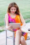 Chica joven que hojea la PC de moda de la tableta Foto de archivo
