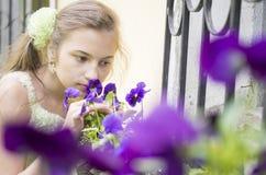 Chica joven que huele las flores hermosas Fotografía de archivo