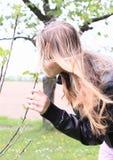 Chica joven que huele un flor Imagenes de archivo