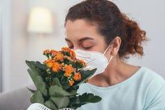 Chica joven que huele una flor en conserva mientras que lleva una máscara respiratoria fotos de archivo