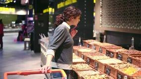 Chica joven que intenta elegir nueces en un supermercado Comprador que pide ayuda metrajes