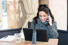 Chica joven que investiga en la tableta y que habla en el smartphone - vista delantera Fotos de archivo libres de regalías