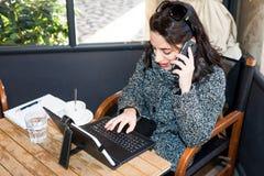 Chica joven que investiga en la tableta y que habla en smartphone Fotografía de archivo libre de regalías