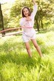 Chica joven que juega con el aro de Hula en campo Fotos de archivo libres de regalías