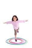 Chica joven que juega con el aro del hula aislado encima Imagen de archivo libre de regalías