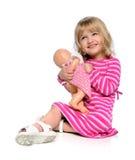 Chica joven que juega con la muñeca Foto de archivo libre de regalías