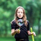 Chica joven que juega con las burbujas de jabón Imagen de archivo
