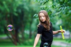 Chica joven que juega con las burbujas de jabón Fotografía de archivo