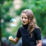 Chica joven que juega con las burbujas de jabón Fotografía de archivo libre de regalías