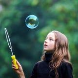 Chica joven que juega con las burbujas de jabón Foto de archivo libre de regalías