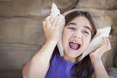 Chica joven que juega con las cáscaras grandes del mar contra sus oídos Imagenes de archivo